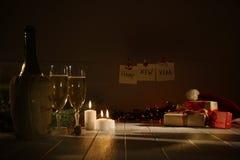 Composizione in inverno La tavola è coperta di vetri di champagne, vino, regali avvolti e ghirlande e candele d'ardore Fotografia Stock Libera da Diritti