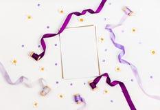Composizione luminosa con i nastri, la camomilla, gli zecchini ed il cristallo di seta su un fondo bianco Spazio per un testo di  Immagini Stock