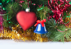 Composizione luminosa con l'albero di Natale, il cuore rosso del giocattolo e la campana blu Immagini Stock