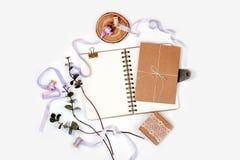 Composizione luminosa con un blocco note a spirale, un eucalyptus, i nastri di seta e una carta kraft su un fondo bianco Foto per Fotografia Stock Libera da Diritti