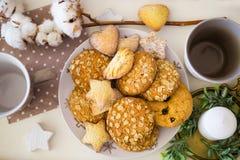 Composizione in Natale con i biscotti, la tazza per caffè e la candela Fotografia Stock