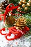 Composizione in Natale con la slitta, il pinecone e la campana Fotografie Stock Libere da Diritti
