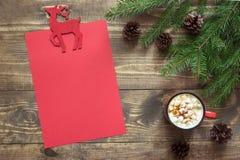 Composizione in Natale con la tazza rossa e lettera in bianco rossa vuota per Santa o le vostre attività di arrivo o di wishlist Immagine Stock