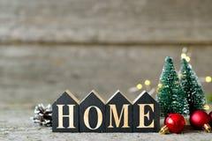 Composizione in Natale con le luci brillanti Le palle rosse, le pigne, giocattolo alloggia la casa del testo sulla Tabella di leg Fotografie Stock