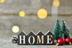 Composizione in Natale con le luci brillanti Le palle rosse, le pigne, giocattolo alloggia la casa del testo sulla Tabella di leg Immagini Stock Libere da Diritti