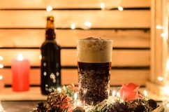 Composizione in Natale con una tazza di birra scura immagine stock