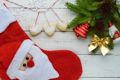 Composizione in Natale: stivali per i regali, ramo dell'abete della decorazione con i giocattoli luminosi, dolci sotto forma di c Fotografia Stock