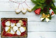 Composizione in Natale: stivali per i regali, ramo dell'abete della decorazione con i giocattoli luminosi, dolci sotto forma di c Fotografie Stock Libere da Diritti