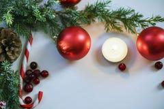 Composizione in Natale su fondo di legno con le palle di Natale e l'albero di Natale verde del ramo con le pigne, candela brucian Immagine Stock
