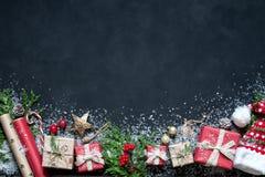 Composizione in Natale sulle decorazioni di Natale di un fondo del nero, scatole, rami dell'albero, cappuccio, Santa, stella Immagine Stock Libera da Diritti