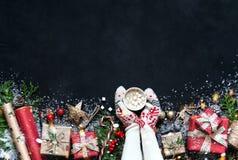Composizione in Natale sulle decorazioni di Natale di un fondo del nero, scatole, rami dell'albero, cappuccio, Santa, stella fotografia stock libera da diritti