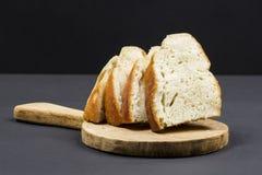 Composizione in natura morta con il tagliere della cucina e le fette di pane di legno Immagini Stock