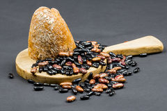 Composizione in natura morta con il tagliere di legno della cucina, fagioli neri e marroni e pane organico Fotografia Stock