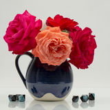 Composizione in natura morta con le rose variopinte, belle, delicate in un vaso ceramico con le pietre dell'agata Fotografie Stock