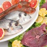 Composizione nel pesce di cousine dell'alimento con l'arancia Fotografie Stock