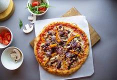 Composizione nella pizza sulla tavola di legno con la mano grigia del fondo immagini stock libere da diritti