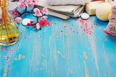 Composizione nella stazione termale con gli asciugamani del cotone, il petrolio dell'aroma, il sale marino e le pietre su fondo b Immagine Stock