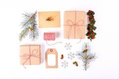 Composizione nella struttura di Natale Natale regalo, ramo del pino, palle rosse, busta, fiocchi di neve di legno bianchi, nastro Immagine Stock