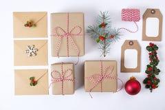 Composizione nella struttura di Natale Natale regalo, ramo del pino, palle rosse, busta, fiocchi di neve di legno bianchi, nastro Immagini Stock