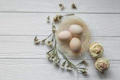 Composizione in Pasqua con le uova ed i petali viola secchi dei fiori Fotografie Stock