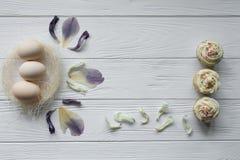 Composizione in Pasqua con le uova ed i petali viola secchi dei fiori Fotografia Stock
