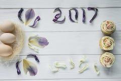Composizione in Pasqua con le uova ed i petali viola secchi dei fiori Iscrizione 2017 Fotografia Stock