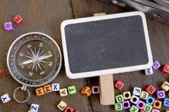 Composizione piana di disposizione della macchina fotografica d'annata, della bussola e del blocco di parole sulla tavola di legn Fotografia Stock