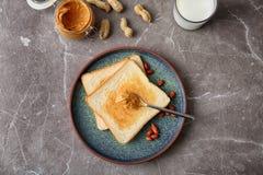 Composizione piana in disposizione con burro di arachidi e pani tostati Fotografia Stock Libera da Diritti