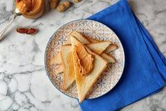 Composizione piana in disposizione con burro di arachidi e pani tostati Immagini Stock Libere da Diritti