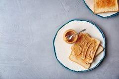Composizione piana in disposizione con burro di arachidi e pani tostati Fotografia Stock