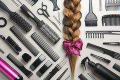 Composizione piana in disposizione con gli strumenti del ` s del parrucchiere e della treccia fotografia stock
