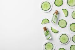 Composizione piana in disposizione con il cetriolo, le bottiglie ed i cuscinetti di cotone freschi su fondo bianco Fotografia Stock Libera da Diritti