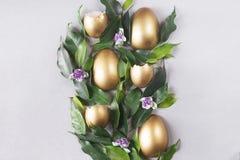 Composizione piana in disposizione con le uova dell'oro Concetto di Pasqua fotografie stock