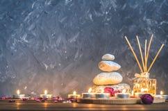 Composizione-pietre della stazione termale, candele, aromaterapia, fiori asciutti Fotografia Stock