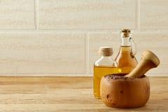 Composizione pittoresca dei barattoli, del pestello e del mortaio dell'olio con erba eterogenea sopra fondo di legno, fuoco selet Immagini Stock Libere da Diritti