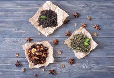 Composizione posta piana con differenti tipi di foglie di tè asciutte su fondo di legno fotografia stock libera da diritti