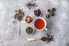 Composizione posta piana con differenti tipi di tè asciutto e di bevande deliziose su fondo grigio immagine stock