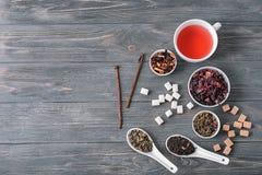 Composizione posta piana con differenti tipi di tè asciutto e di bevande deliziose su fondo di legno fotografia stock libera da diritti