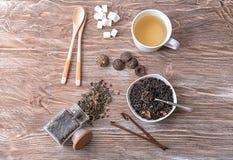 Composizione posta piana con differenti tipi di tè asciutto e di bevande deliziose su fondo di legno fotografie stock libere da diritti