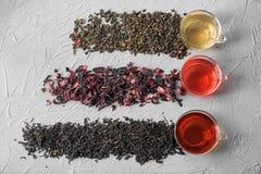 Composizione posta piana con differenti tipi di tè e di tazze asciutti su fondo grigio fotografia stock