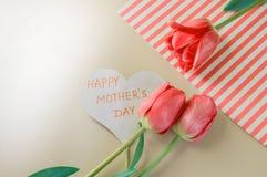 Composizione posta piana con i fiori e cuore per mother' giorno di s, accogliente per le donne Tulipani rossi su fondo rosa immagini stock libere da diritti