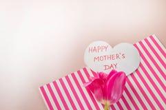Composizione posta piana con i fiori e cuore per mother' giorno di s, accogliente per le donne Tulipani rossi su fondo rosa fotografia stock
