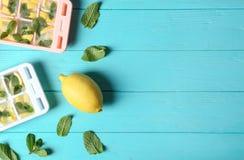 Composizione posta piana con il vassoio, la menta ed il limone del cubetto di ghiaccio su fondo di legno immagini stock