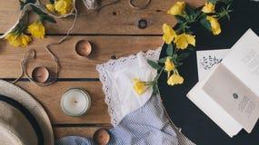 Composizione romantica che consiste delle candele dell'aroma, dei fiori gialli, del libro e della cartolina sulla tavola di legno Immagini Stock Libere da Diritti