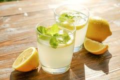 Composizione rustica con limonata fredda casalinga di recente schiacciata in bottiglia e vetri con le goccioline di condensazione Immagine Stock Libera da Diritti