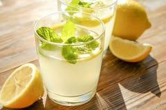 Composizione rustica con limonata fredda casalinga di recente schiacciata in bottiglia e vetri con le goccioline di condensazione Immagine Stock