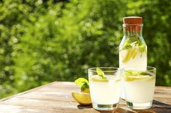 Composizione rustica con limonata fredda casalinga di recente schiacciata in bottiglia e vetri con le goccioline di condensazione Fotografia Stock Libera da Diritti