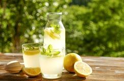 Composizione rustica con limonata fredda casalinga di recente schiacciata in bottiglia e vetri con le goccioline di condensazione Immagini Stock Libere da Diritti