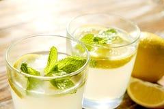 Composizione rustica con limonata fredda casalinga di recente schiacciata in bottiglia e vetri con le goccioline di condensazione Fotografie Stock