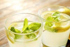 Composizione rustica con limonata fredda casalinga di recente schiacciata in bottiglia e vetri con le goccioline di condensazione Immagini Stock